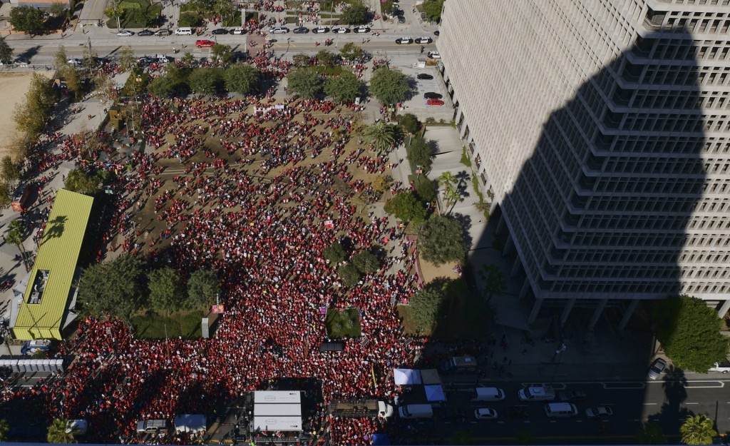 The shadow of Los Angeles City Hall is cast on a building while striking Los Angeles Unified teachers gather in Grand Park in Los Angeles on Tuesday, ...