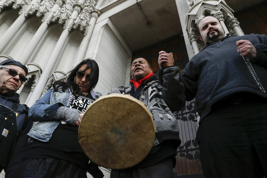 Native American protestors hold hands with parishioner Nathanial Hall, right, during a group prayer outside the Catholic Diocese of Covington Tuesday,