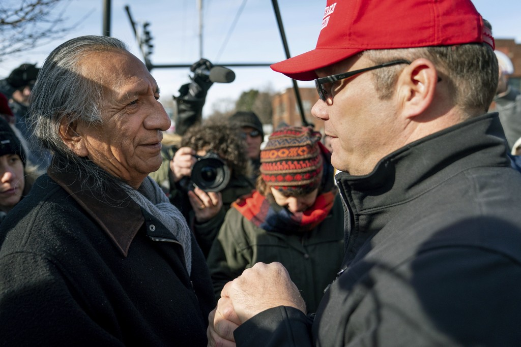 Guy Jones, left, and a supporter of President Donald Trump named Don join hands during a gathering of Native American supporters in front of the Catho