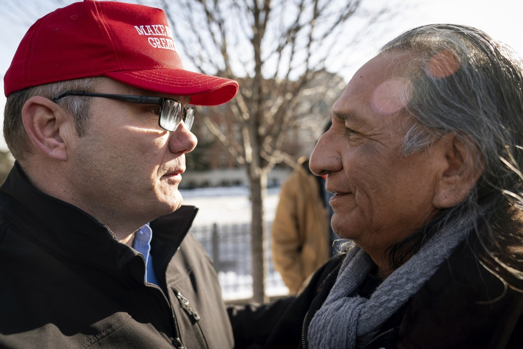 Guy Jones, left, and a supporter of President Donald Trump named Don embrace during a gathering of Native American supporters in front of the Catholic