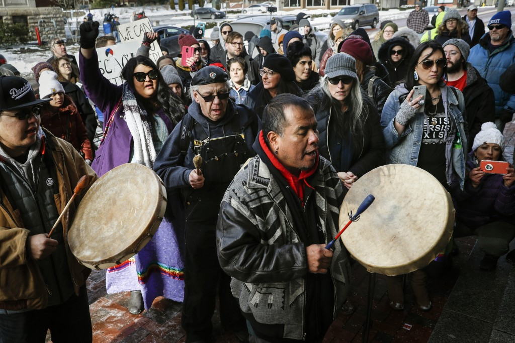 A protestor leads a Native American prayer with a traditional drum outside the Catholic Diocese of Covington Tuesday, Jan. 22, 2019, in Covington, Ky.