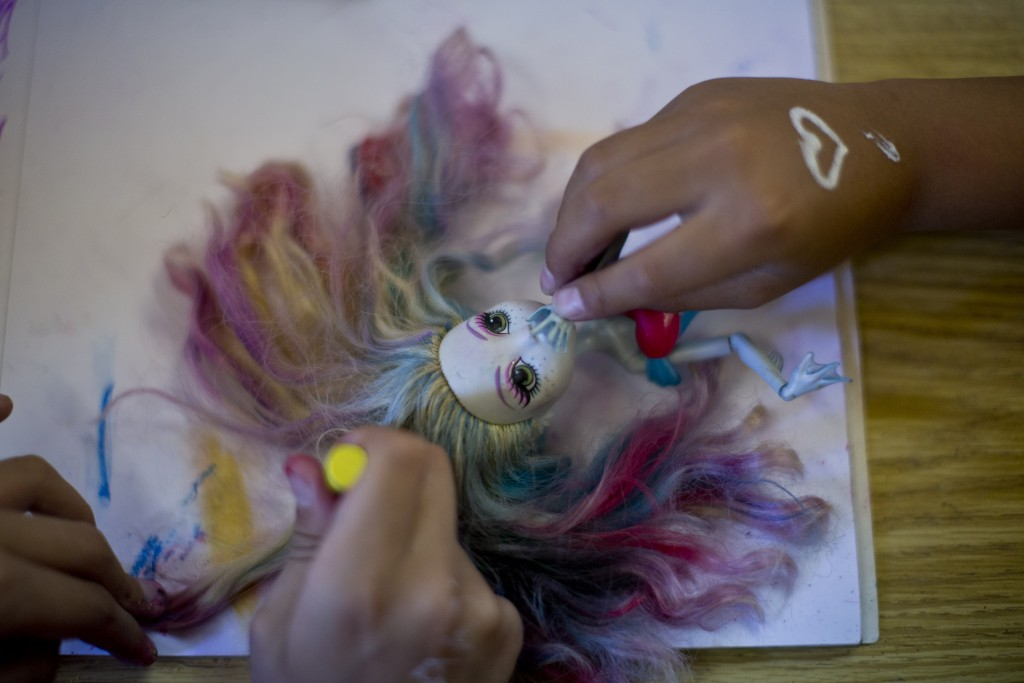 In this Dec.12, 2018 photo, transgender girls plays with a doll at the Amaranta Gomez school in Santiago, Chile. Although space is limited, parents sa