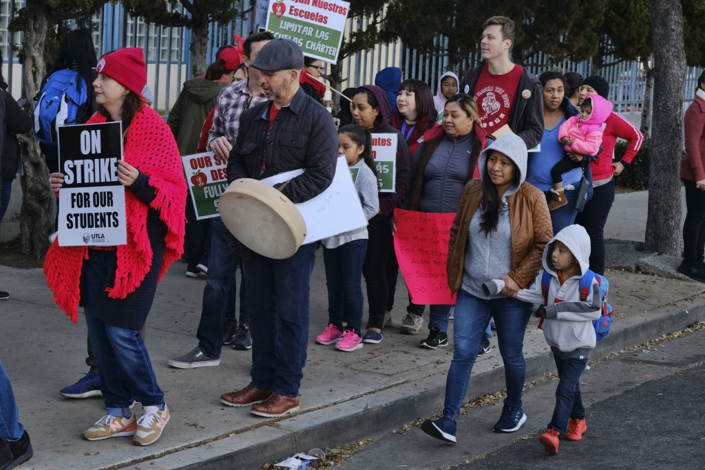 A parent arrives bringing her child to school while striking Los Angeles Unified District teachers rally in front of Evelyn Thurman Gratts Elementary ...