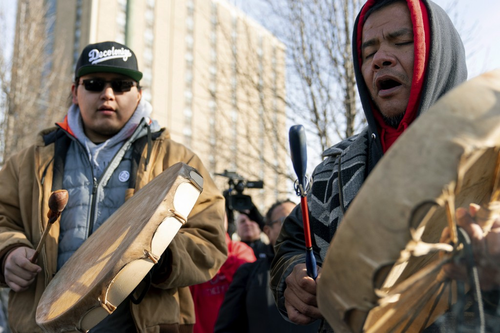 Sleepy Eye Lafromboise, right, and his son Eshtakaba, both of the Sioux Nation, sing during a gathering of Native American supporters in front of the