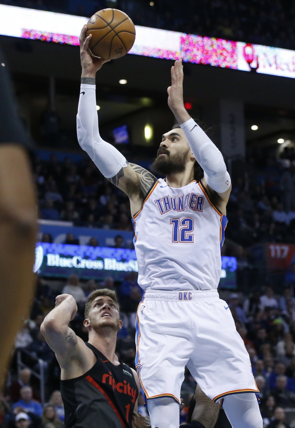 Oklahoma City Thunder center Steven Adams (12) goes to the basket in front of Portland Trail Blazers forward Meyers Leonard, left, in the first half o...