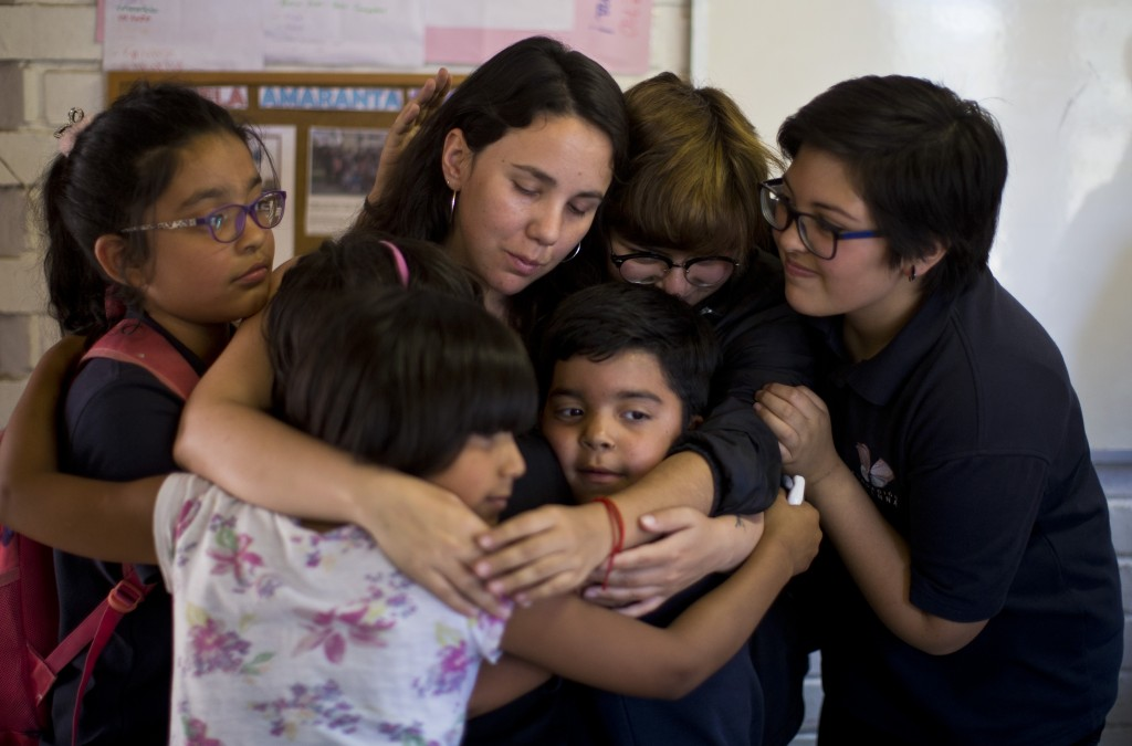 In this Dec.12, 2018 photo, transgender children embrace teacher Teani Cortes during the last day of school at the Amaranta Gomez school in Santiago,