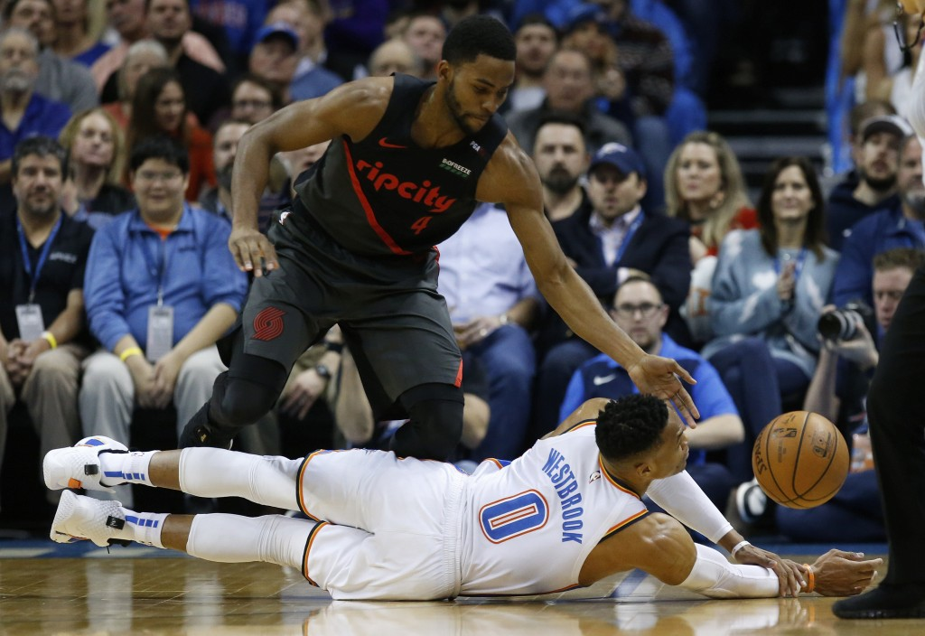 Oklahoma City Thunder guard Russell Westbrook (0) reaches for a loose ball in front of Portland Trail Blazers forward Maurice Harkless (4) in the firs...