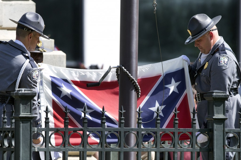FILE - In this July 10, 2015, file photo, members of an honor guard from the South Carolina Highway patrol lower the Confederate battle flag as it is