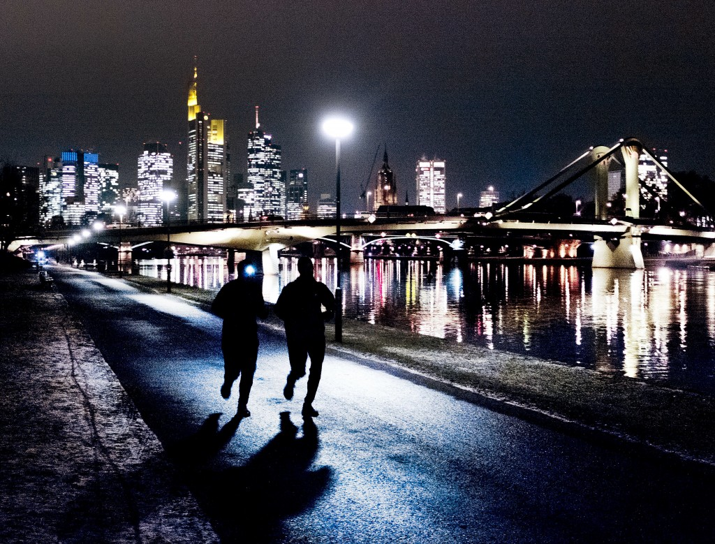 Two men run along the river Main with the buildings of the banking district in the background in Frankfurt, Germany, Tuesday, Jan. 22, 2019. (AP Photo...
