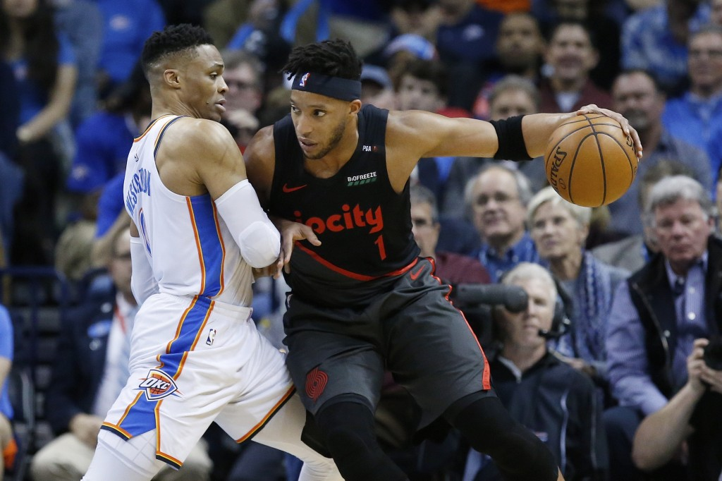 Portland Trail Blazers guard Evan Turner (1) drives against Oklahoma City Thunder guard Russell Westbrook, left, in the first half of an NBA basketbal...