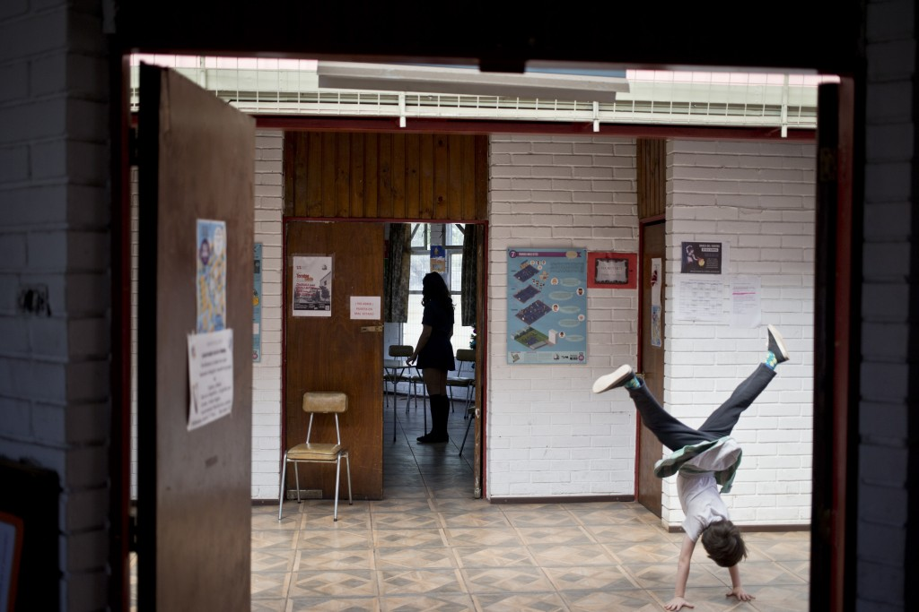 In this Dec.13, 2018 photo, Aurora, a transgender girl, does cartwheels in the Amaranta Gomez school, in Santiago, Chile. Activists and parents of tra