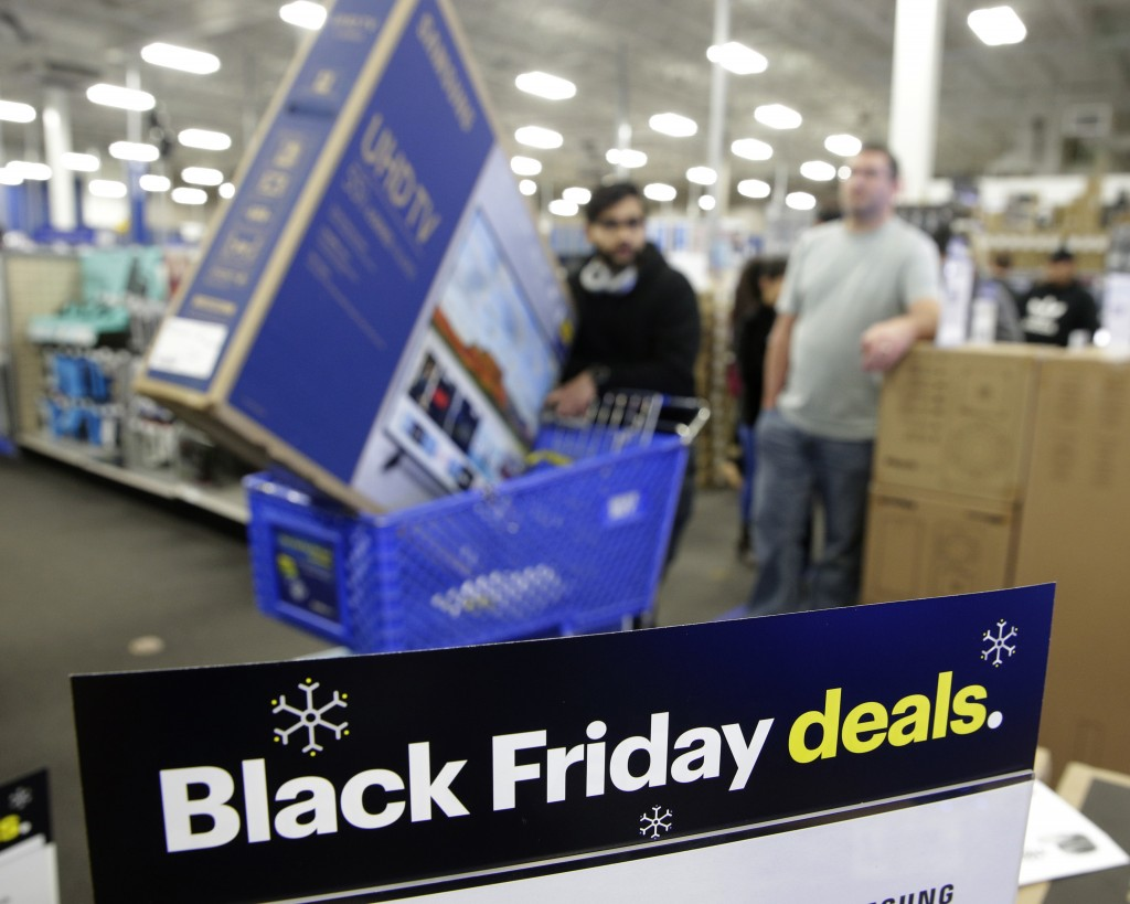 FILE- In this Nov. 22, 2018, file photo people wait in line to buy televisions as they shop during an early Black Friday sale at a Best Buy store on T...