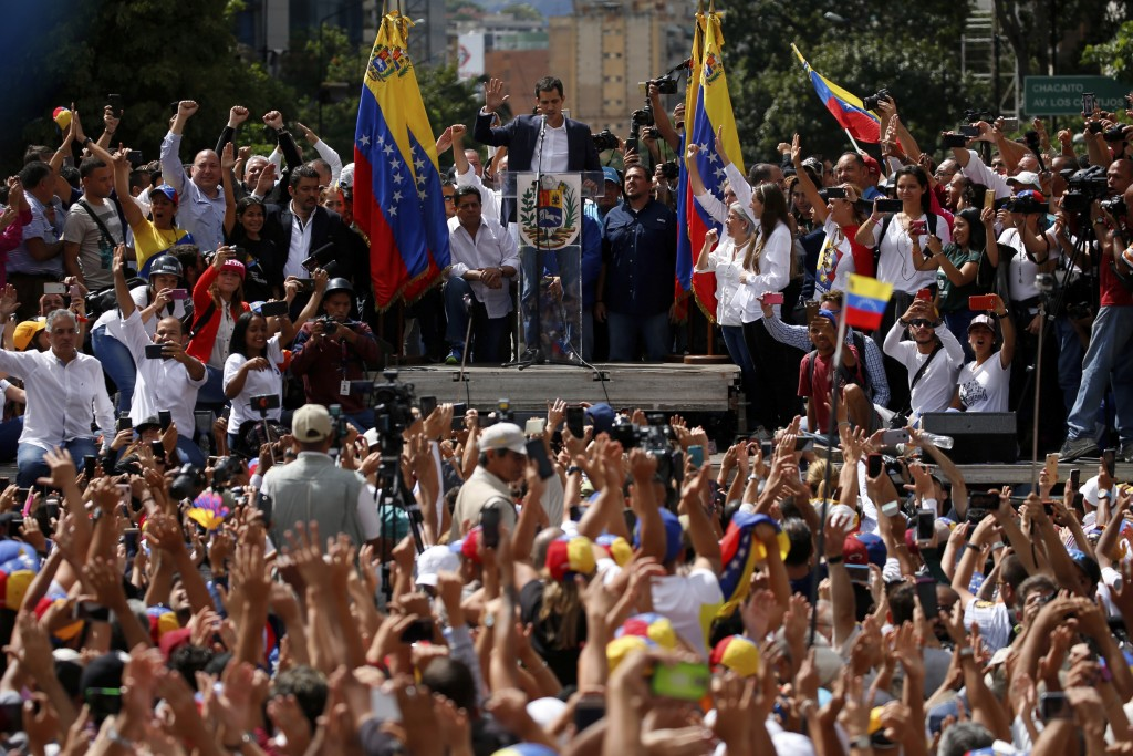 Juan Guaido, head of the opposition-run congress, looks down and holds up his hand during his symbolic swearing-in as interim president of Venezuela o