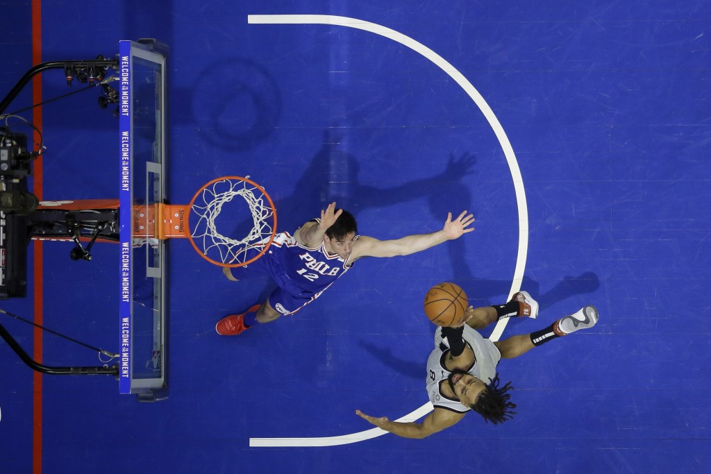 San Antonio Spurs' Patty Mills, right, goes up for a shot against Philadelphia 76ers' T.J. McConnell during the first half of an NBA basketball game, ...