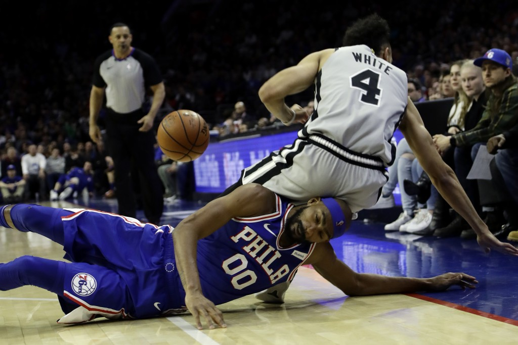 Philadelphia 76ers' Corey Brewer (00) collides with San Antonio Spurs' Derrick White (4) chasing after a loose ball during the first half of an NBA ba...