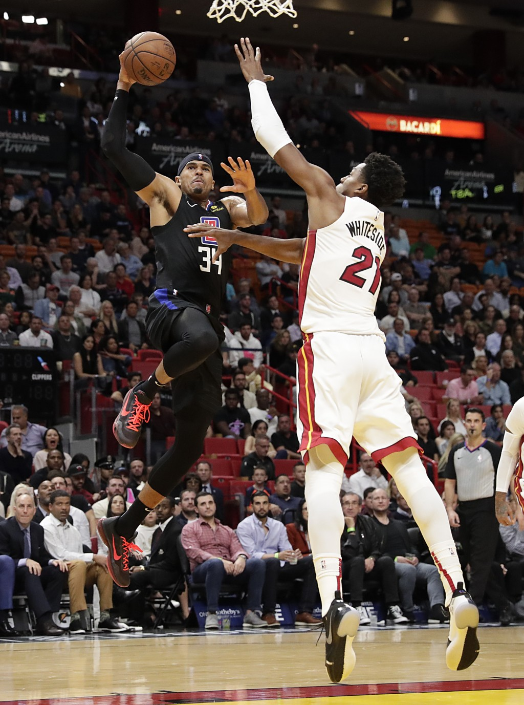 Los Angeles Clippers forward Tobias Harris is fouled by Miami Heat center Hassan Whiteside during the first half of an NBA basketball game, Wednesday,...