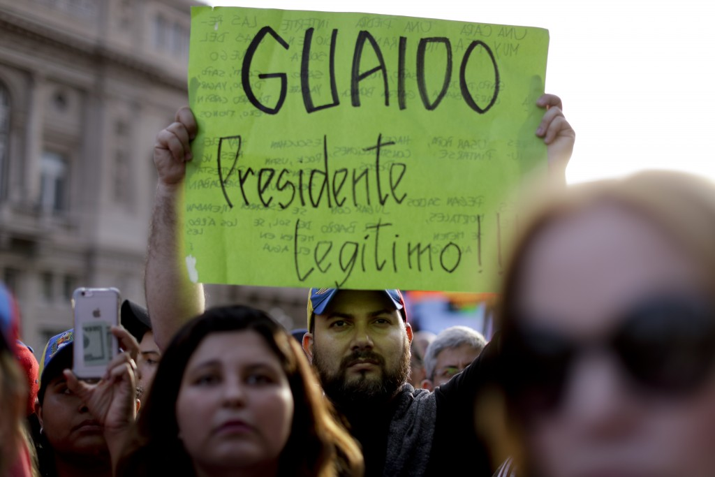 """A Venezuelan anti-government protester holds a sign that reads in Spanish """"Guaido legitimate President!"""" during a demonstration in Buenos Aires, Argen"""