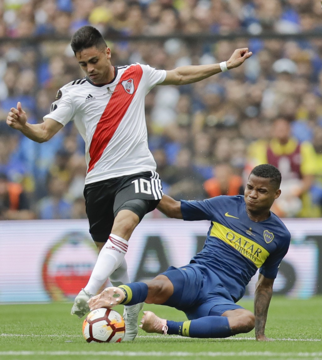 FILE - In this Nov. 11, 2018, file photo, Gonzalo Martinez of Argentina's River Plate (10) and Wilmar Barrios of Argentina's Boca Juniors battle for t...