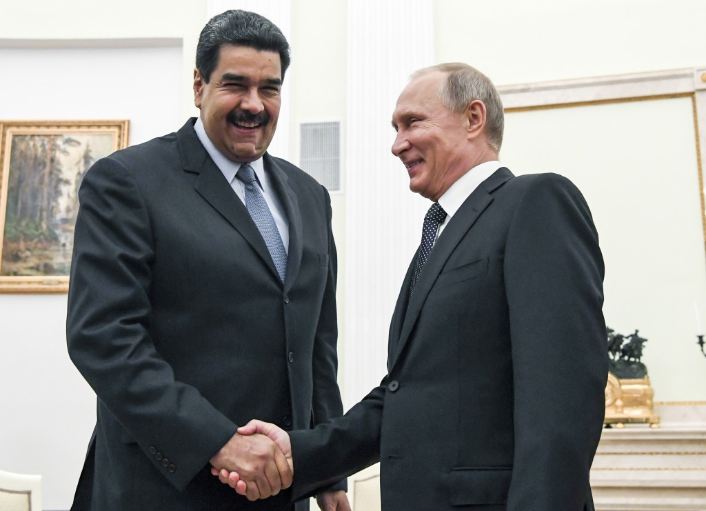 FILE - In this file pool photo taken on Oct. 4, 2017, Russian President Vladimir Putin, right, shakes hands with Venezuela's President Nicolas Maduro ...