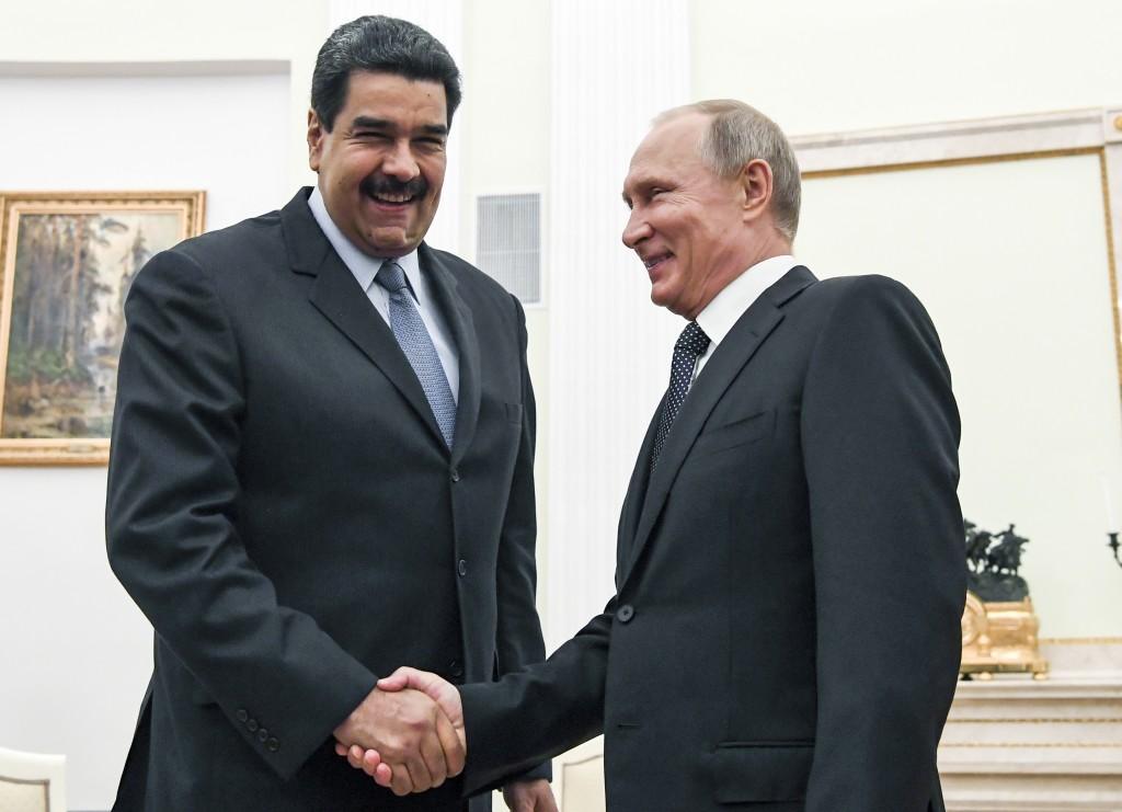 FILE - In this file pool photo taken on Oct. 4, 2017, Russian President Vladimir Putin, right, shakes hands with Venezuela's President Nicolas Maduro
