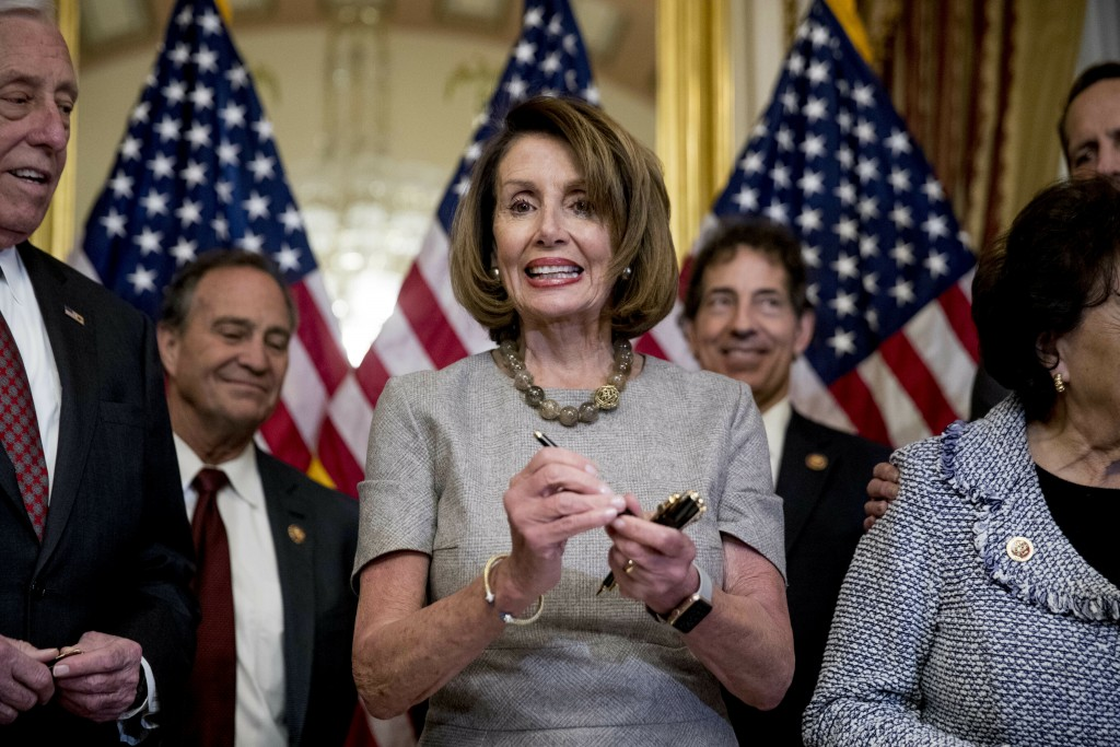 House Speaker Nancy Pelosi of Calif., accompanied by House Democratic members stand after signs a deal to reopen the government on Capitol Hill in Was
