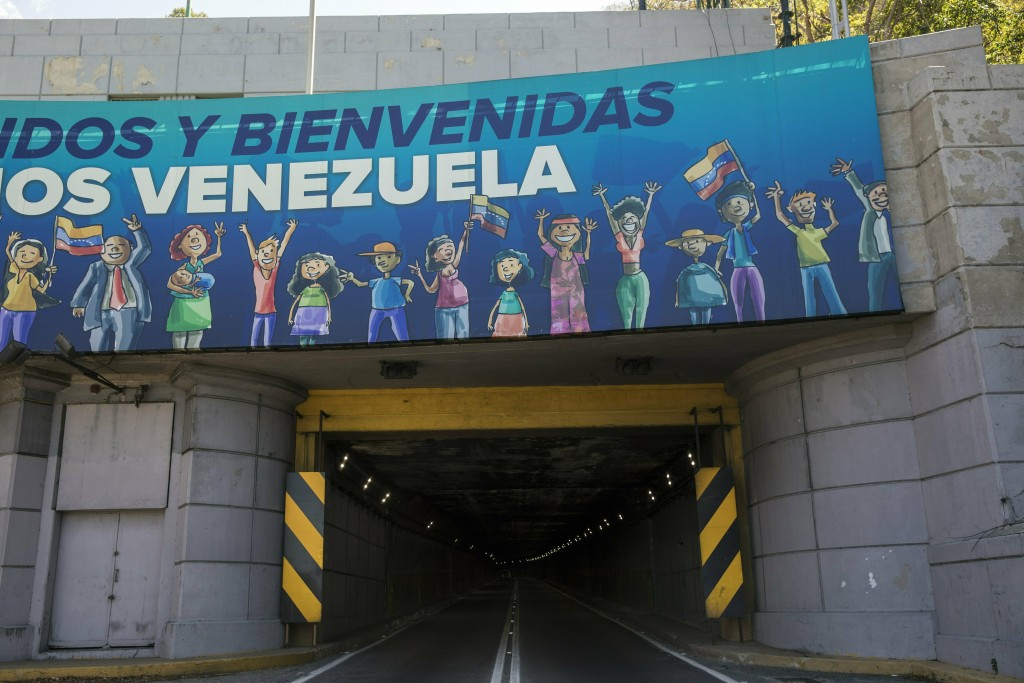 """A banner carries the Spanish message: """"Welcome to Venezuela"""" at the entrance of a tunnel along the road that connects La Guaira, where the Simon Boliv..."""