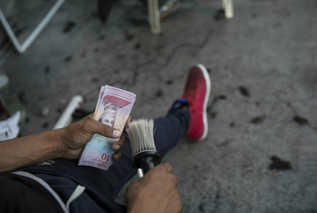 Barber Juan Manuel Marquez rests after charging 1000 bolivars or around .50 cents US, for a haircut at a makeshift barber shop on a sidewalk in Caraca...