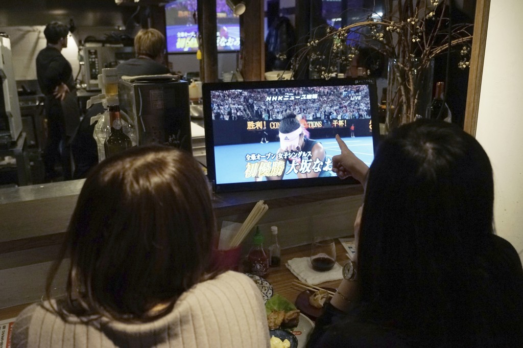 Customers at a restaurant in Tokyo watch the TV monitor at the end of the Australian Open tennis women's final between Naomi Osaka of Japan and Petra