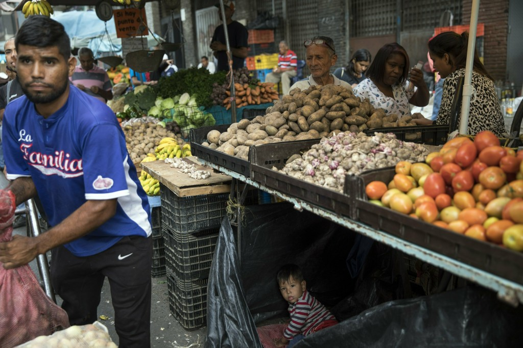 Vendors wait for customers at the Quinta Crespo street market downtown in Caracas, Venezuela, Saturday, Jan. 26, 2019. The country's political showdow...