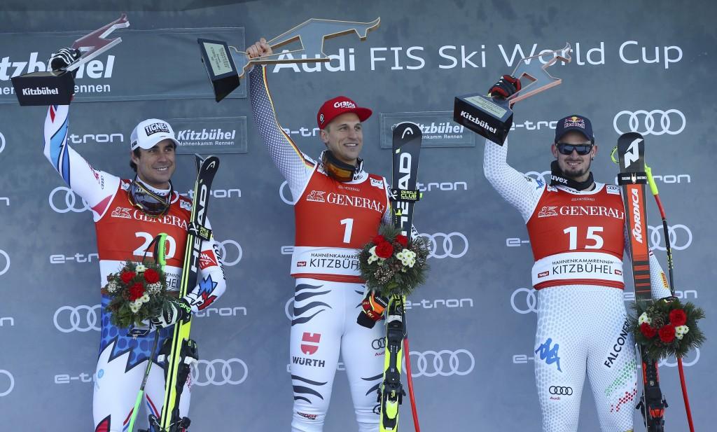 Germany's Josef Ferstl, center, winner of the alpine ski, men's World Cup super-G, celebrates on the podium with second placed France's Johan Clarey, ...