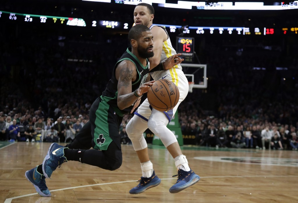 Boston Celtics guard Kyrie Irving, bottom, drives against Golden State Warriors guard Stephen Curry, top, in the first quarter of an NBA basketball ga
