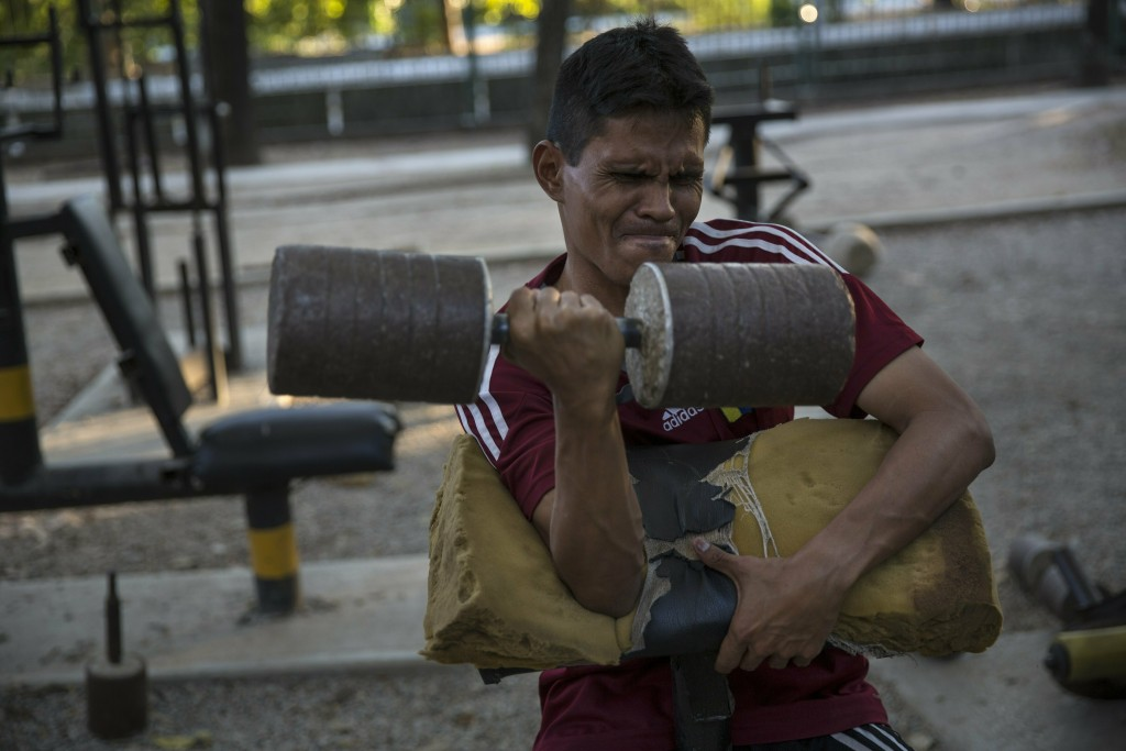 A man lift weights in a makeshift gym at Los Caobos public park in Caracas, Venezuela, Saturday, Jan. 26, 2019. The United States urged all nations Sa...