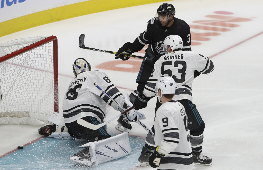Metropolitan Division's Seth Jones, top, of the Columbus Blue Jackets, scores a goal past Atlantic Division's Andrei Vasilevskiy, left, of the Tampa B