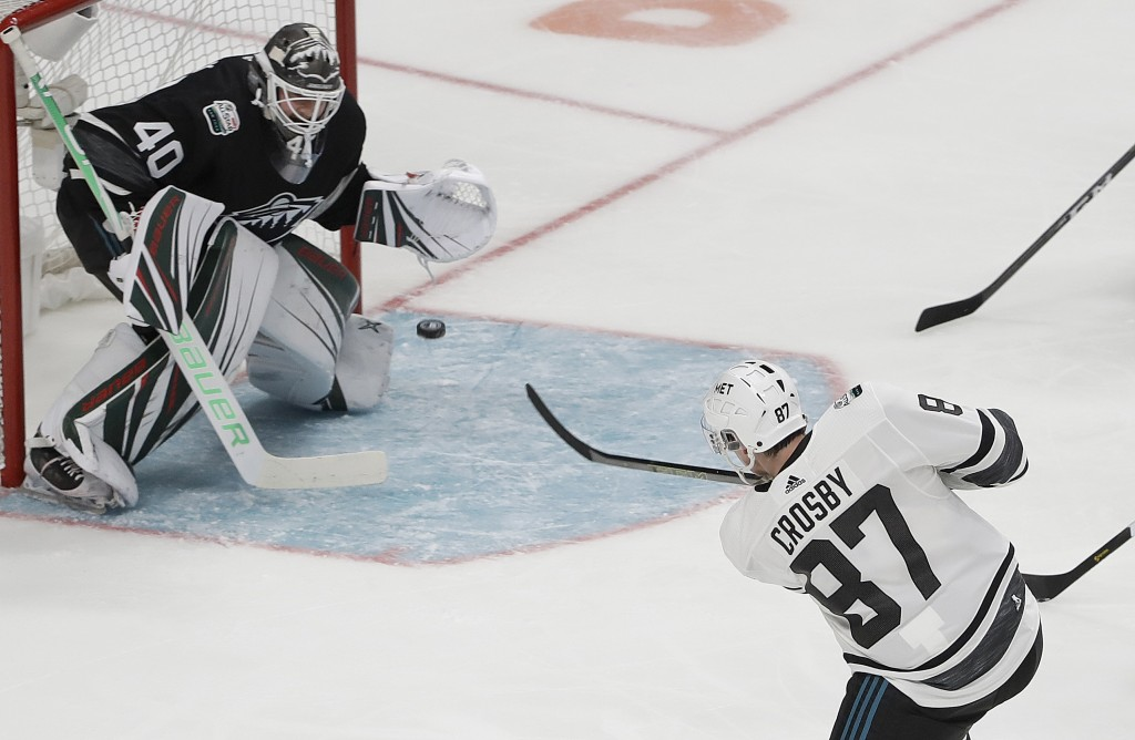Metropolitan Division's Sidney Crosby, of the Pittsburgh Penguins, scores a goal past Central Division's Devan Dubnyk, of the Minnesota Wild, during t