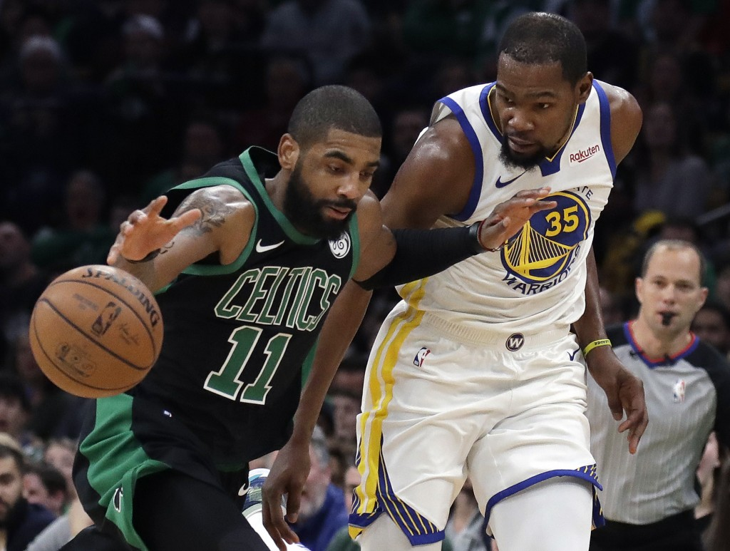 Boston Celtics guard Kyrie Irving (11) dribbles against Golden State Warriors forward Kevin Durant (35) in the first quarter of an NBA basketball game