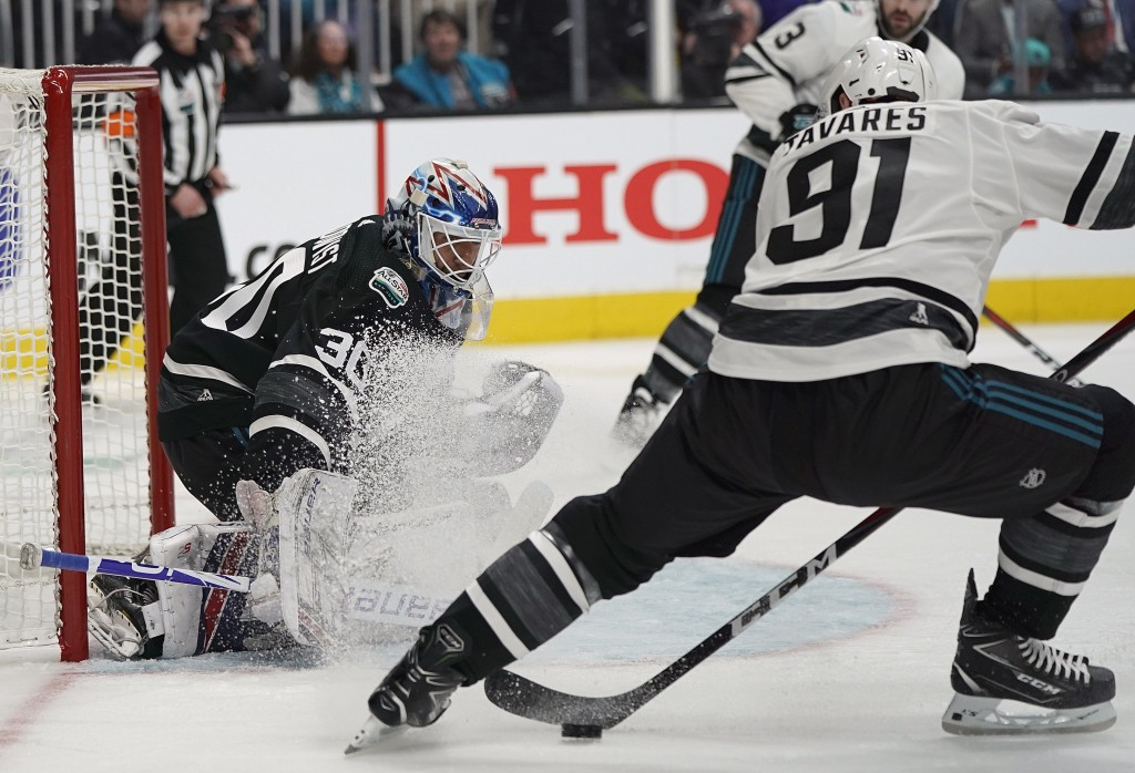 Metropolitan Division's Henrik Lundqvist, left, of the New York Rangers, defends the goal in front of Atlantic Division's John Tavares, of the Toronto