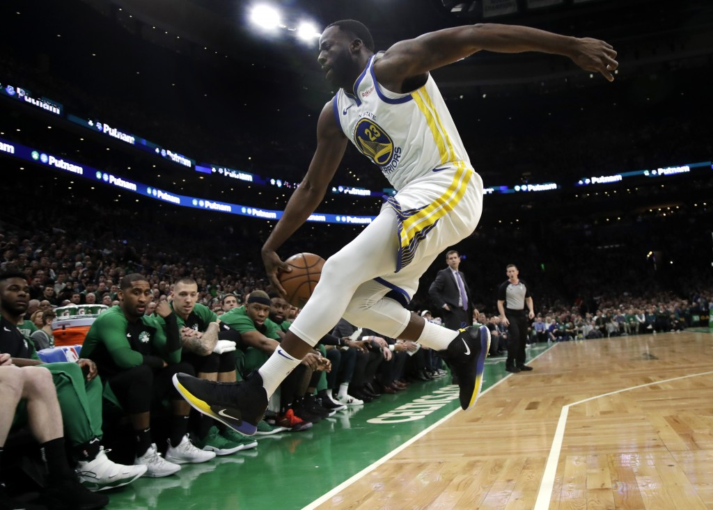 Golden State Warriors forward Draymond Green (23) jumps to save the ball from going out of bounds in front of the Boston Celtics bench in the first qu