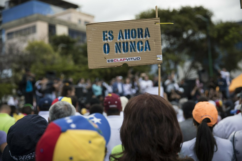 """A member of the opposition holds a sign with message that reads in Spanish:""""It's now or never"""", during a rally to propose amnesty laws for police and ..."""