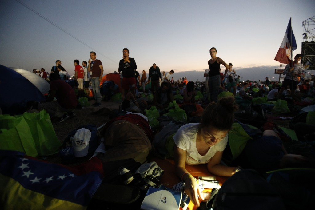 Youth begin to wake after camping out in the metro park Campo San Juan Pablo II, in Panama City, Sunday, Jan. 27, 2019, where Pope Francis will celebr