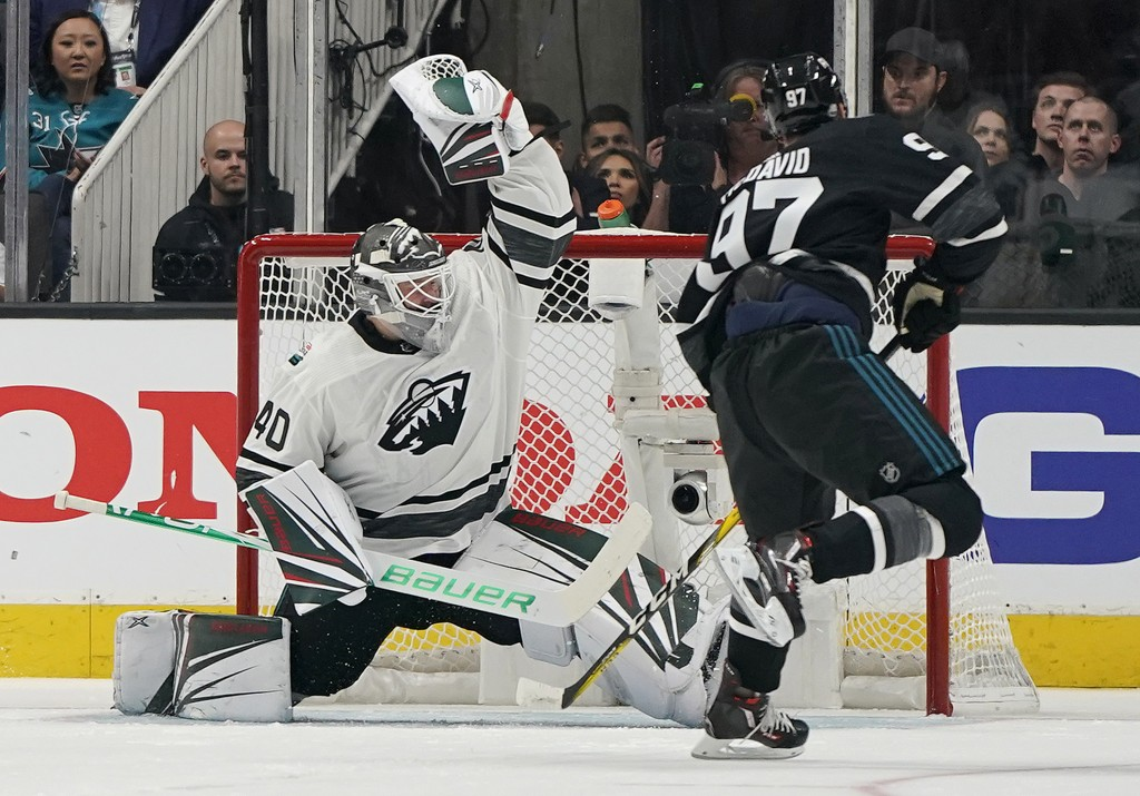 Central Division's Devan Dubnyk, left, of the Minnesota Wild, defends the net against Pacific Division's Connor McDavid, of the Edmonton Oilers, durin
