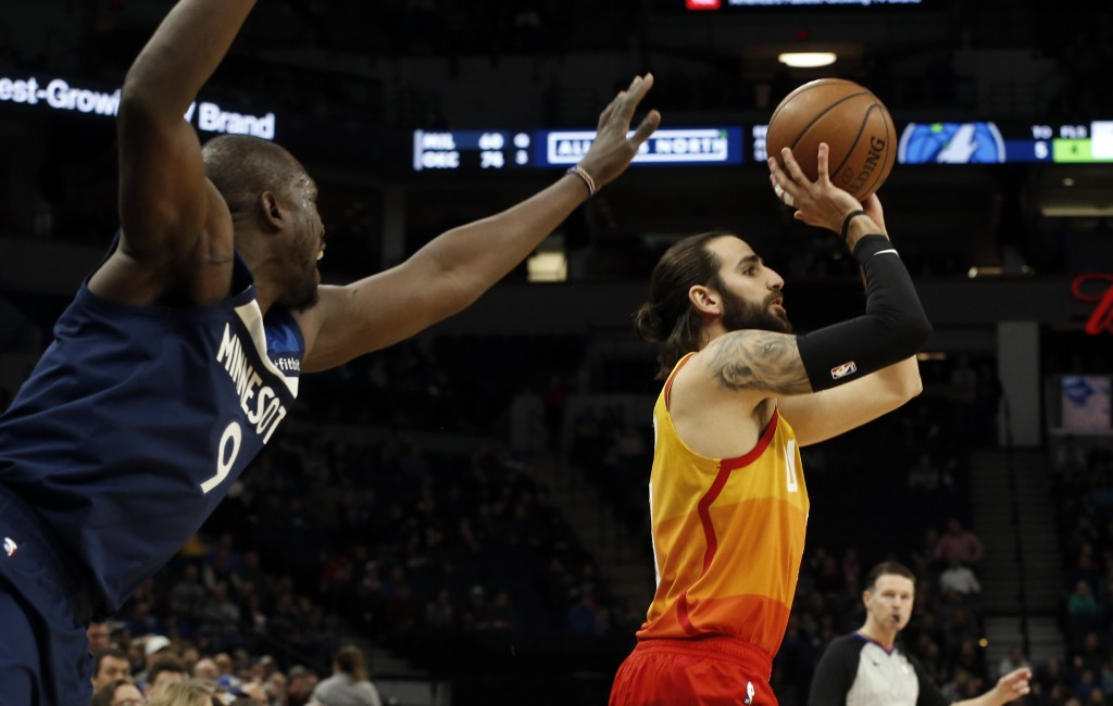 Minnesota Timberwolves' Luol Deng, left, looms in as Utah Jazz's Ricky Rubio, of Spain, shoots in the first half of an NBA basketball game Sunday, Jan...