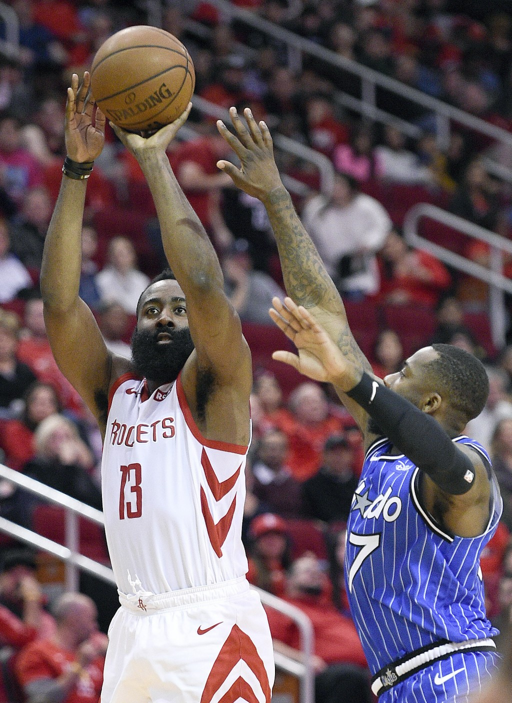Houston Rockets guard James Harden (13) shoots as Orlando Magic forward Jonathon Simmons defends during the second half of an NBA basketball game, Sun...