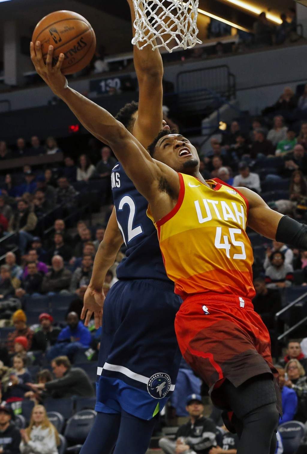 Utah Jazz's Donovan Mitchell, right, lays up a shot as Minnesota Timberwolves' Karl-Anthony Towns defends in the first half of an NBA basketball game ...