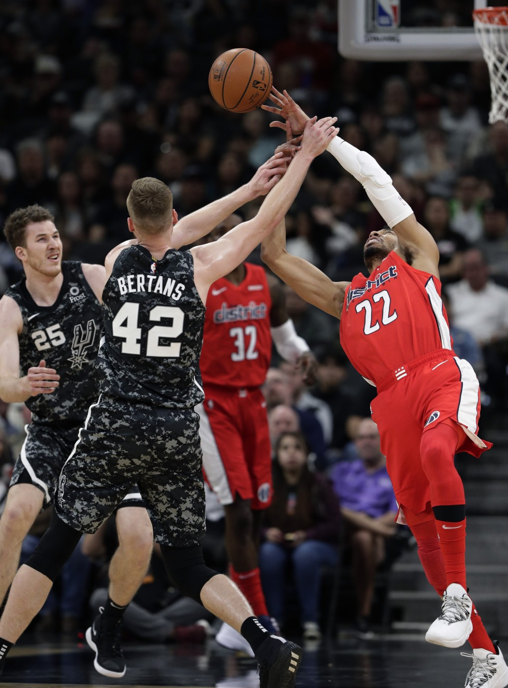 Washington Wizards forward Otto Porter Jr. (22) is fouled by San Antonio Spurs forward Davis Bertans (42) as he reaches for the ball during the first ...