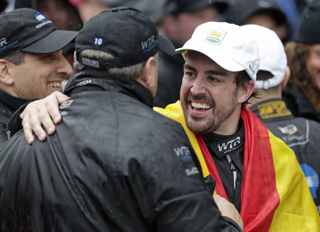 Fernando Alonso,right, of Spain, celebrates with crew members after winning the IMSA 24-hour race at Daytona International Speedway, Sunday, Jan. 27, ...