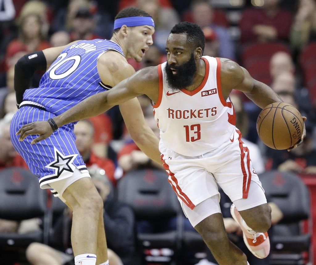 Houston Rockets guard James Harden (13) dribbles around Orlando Magic forward Aaron Gordon during the first half of an NBA basketball game, Sunday, Ja