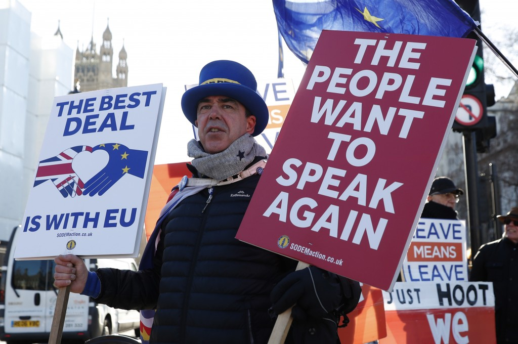 Anti Brexit protester Steve Bray who is almost permanently demonstrating outside the Houses of Parliament watches the traffic as he holds up placards ...