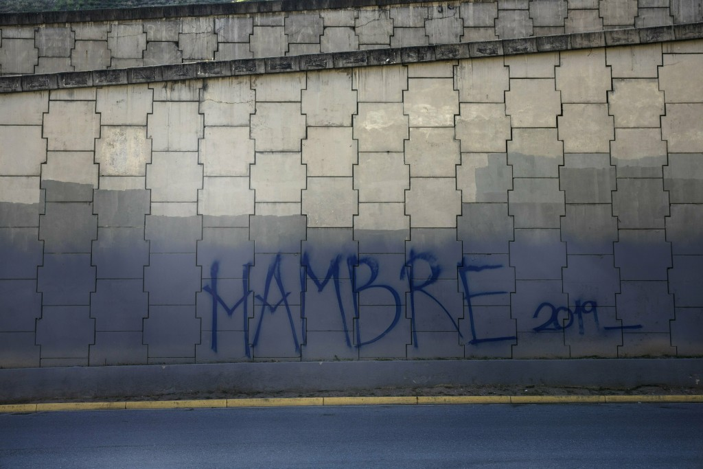 """Graffiti that reads in Spanish: """"Hunger 2019"""" covers a highway wall in Caracas, Venezuela, Sunday, Jan. 27, 2019. Venezuelans are struggling with hype..."""
