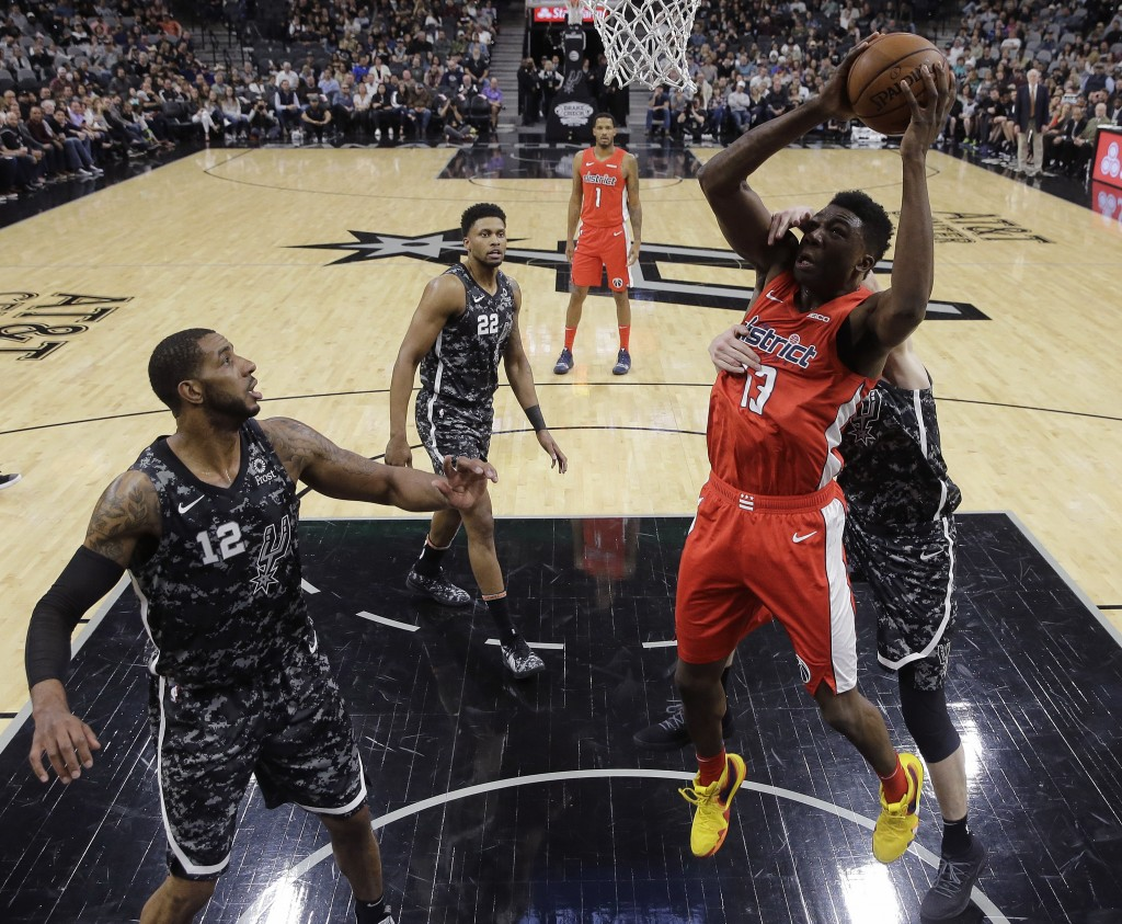 Washington Wizards center Thomas Bryant (13) is fouled by San Antonio Spurs forward Davis Bertans, right, during the first half of an NBA basketball g...