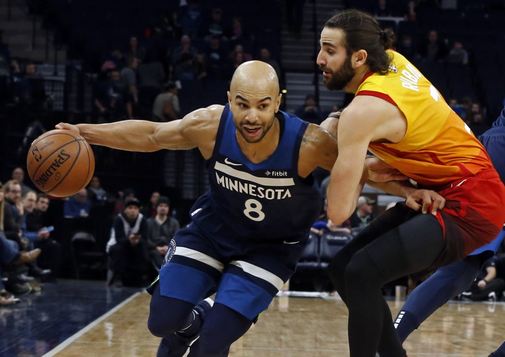 Minnesota Timberwolves' Jerryd Bayless, left, gets tangled up with Utah Jazz's Ricky Rubio of Spain in the second half of an NBA basketball game Sunda...